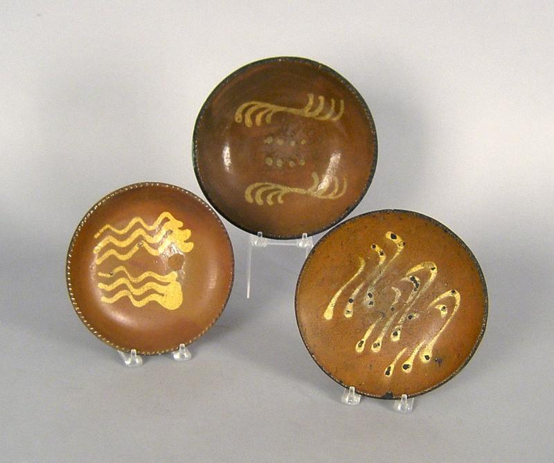 Three slip decorated redware plates, 19th c., 7 1/