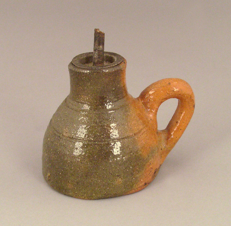 Redware oil lamp, ca. 1900, with green and orangel
