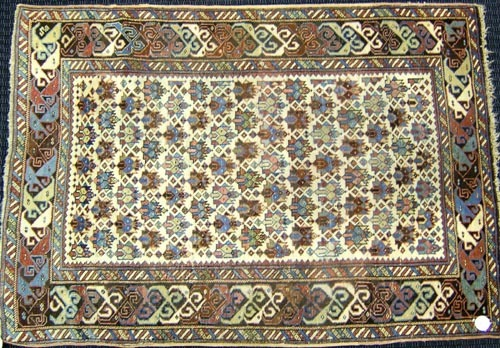Shirvan throw rug, ca. 1910, with an ivory field a