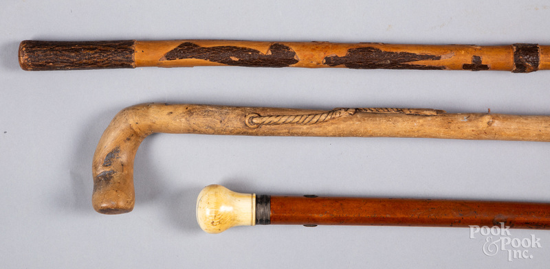 Two carved canes, together with a bone grip cane.