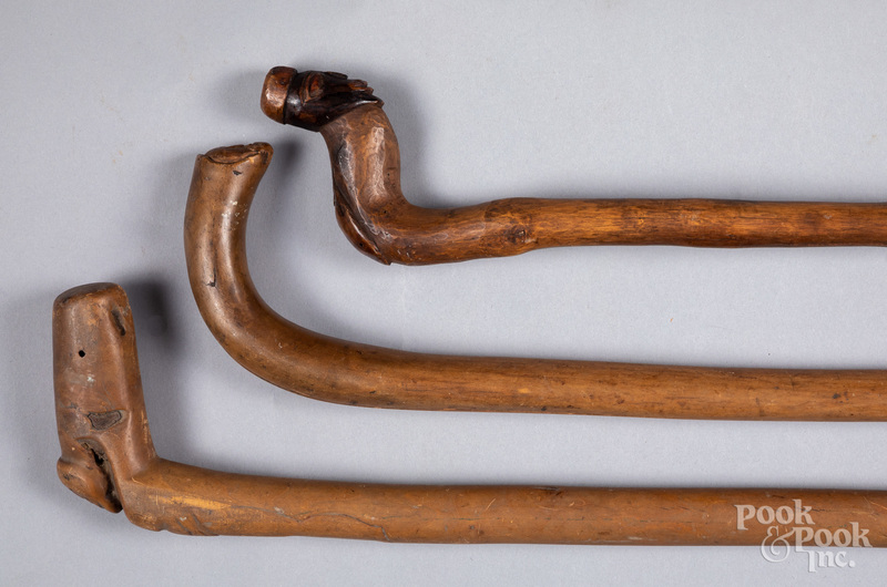 Three carved canes with figural grips.