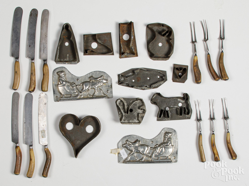 Tin cookie cutters, together with flatware