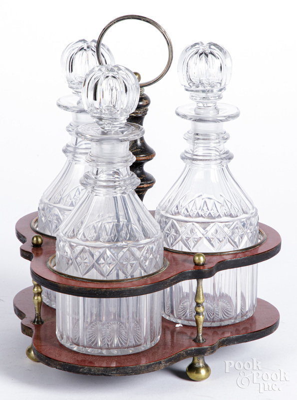 Red lacquer cruet stand, with cut glass bottles.