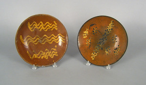 Two slip decorated redware plates, 19th c., 10 1/4