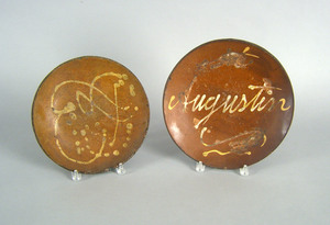 Two slip decorated redware chargers, 19th c., onen