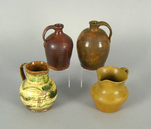Two redware jugs, together with two pitchers, tall