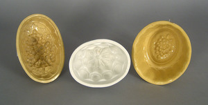 Two yelloware molds, together with a white ironsto