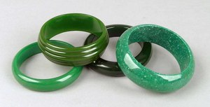 Four green bakelite bangles to include a grooved e