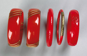 Five red bakelite bangles, 2 carved and 3 with bra