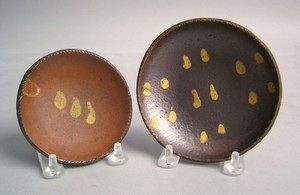 Two redware cup plates, 19th c., with yellow slipe