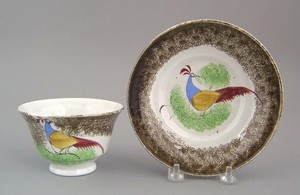 Brown spatter cup and saucer, 19th c., with peafow