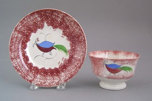Red spatter cup and saucer, 19th c., with guinea h