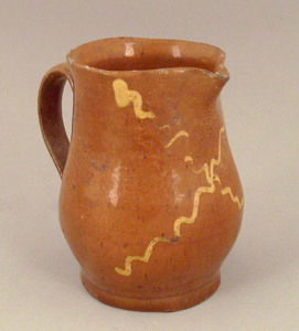 Redware creamer, 19th c., with yellow squiggle lin