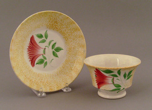 Yellow spatter cup and saucer, 19th c., with thist