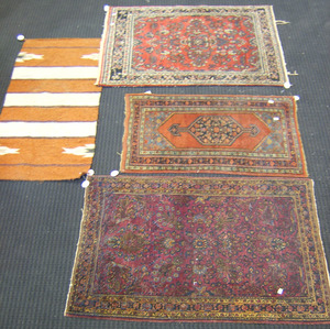 Three oriental mats, together with a flatweave bla