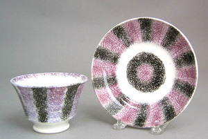 Purple and black rainbow spatter cup and saucer.