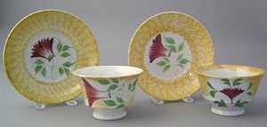 Yellow spatter cup and saucer with red thistle, to