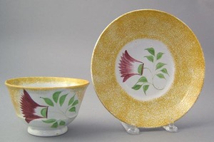 Yellow spatter cup and saucer with red thistle.