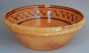 Large Moravian earthenware bowl with orange glazei
