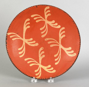 Redware pie plate, 19th c., with yellow slip cross