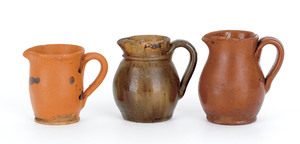 Three redware creamers, 19th c., one with manganes