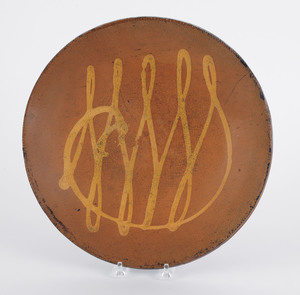 Redware charger, 19th c., with yellow slip loop de