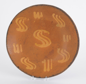 Redware charger, 19th c., with yellow slip S motif