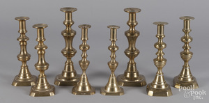 Four pairs of English brass candlesticks.