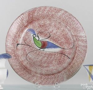 Red spatter plate with green, red and blue peafowl