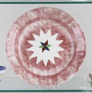 Red spatter plate with red, blue and green star in