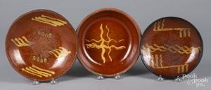 Three slip decorated redware plates/shallow bowls