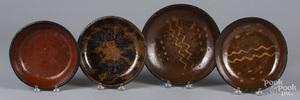 Four redware plates/shallow bowls