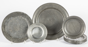 Eleven pewter plates and a charger, etc.