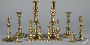 Six pairs of brass candlesticks
