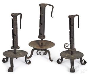 Three wrought iron adjustable candlesticks