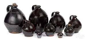 Nine graduated redware manganese glaze ovoid jugs