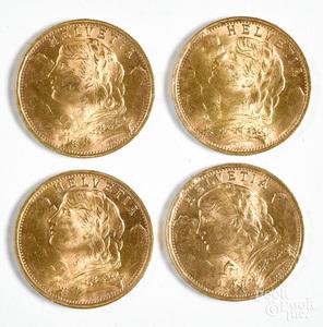 Four Helvetia 20 Franc gold coins.