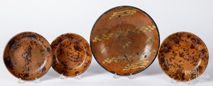 Four redware plates and shallow bowls