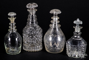 Four colorless glass decanters