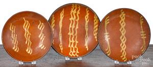 Three Pennsylvania slip decorated redware plates