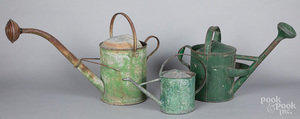 Three green painted tin watering cans