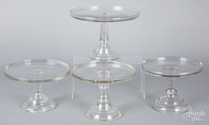 Four colorless glass cake stands