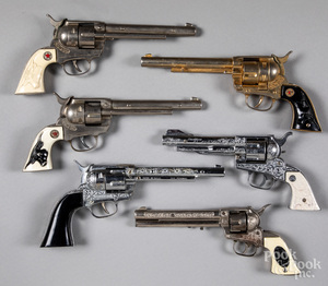 Six toy cap guns with rotating cylinders