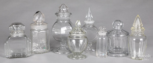 Eight colorless glass candy or apothecary bottles