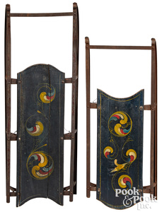 Two similar painted sleds, with swirl decoration